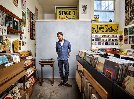 Young entrepreneur poses for photo to develop branding in record store