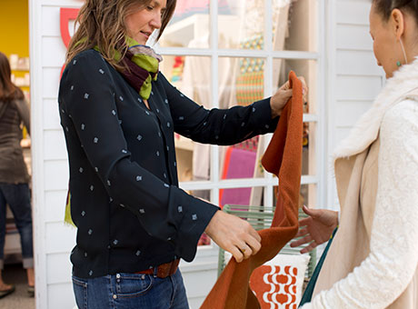Two women inspect clothing at retail business
