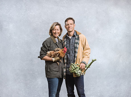 Farm employees running senior care business pose for photo holding vegetables and crops