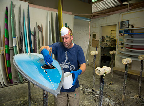 Employee at small business surf shop scrubs board in workshop