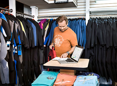 Surf shop owner reviews activity-based costing on laptop computer near racks of clothing