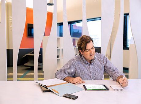 Man in business office reviews financial statements on tablet sitting at table near client folders