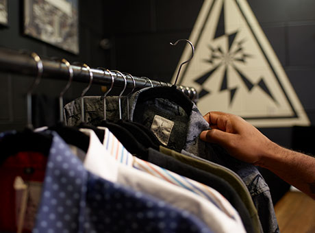 Man sorting clothing inventory on racks in retail store