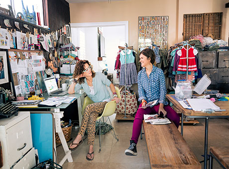Two women in retail store room discuss hurdle rates for new projects near racks of clothing and computer desk