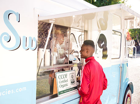 Small retail business owner on food truck serving customer at window