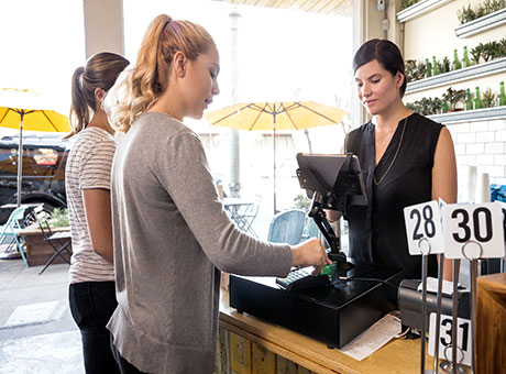 Restaurant manager at register upsells merchandise to customers processing transaction