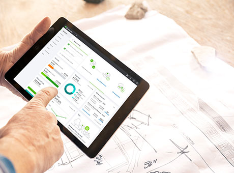 Man holding tablet with view of tax developments next to blueprints