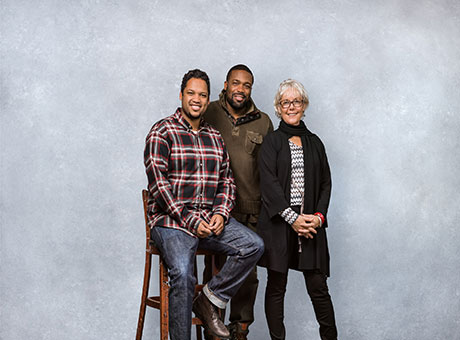 Small business owners pose for photo in front of grey background