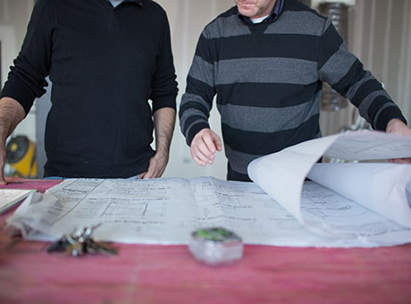 Two contractors operating a trade business review blueprints at job site
