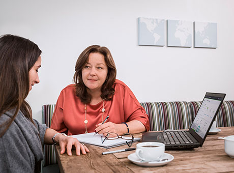 Accountant and employee discuss the process of three-way matching at office table near laptop