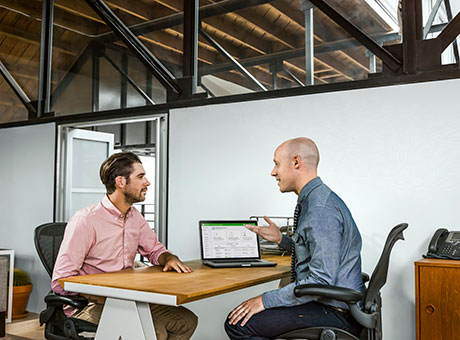 Small business owner and accountant discuss financial controls sitting at office desk near computer
