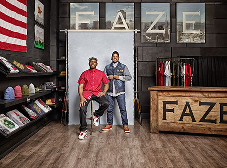 Two corporate business owners in clothing retail shop pose for photo