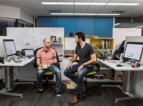 Two men in office cubicle discuss incident response plans near computers