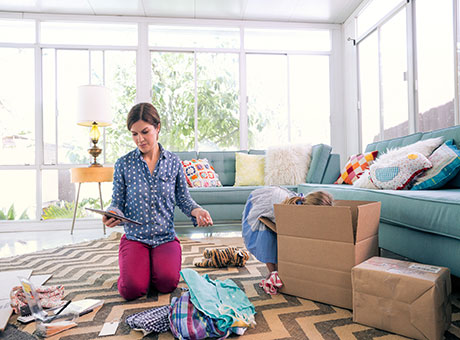 Home-based freelancer reviews fair market value on tablet while sorting through boxes of clothing