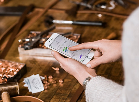 Small business owner views scheduled billing on mobile device near table with jewelry
