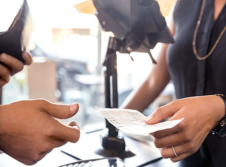Female in restaurant hands receipt to customer at register for a cross-promotion
