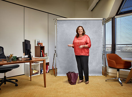 Accountant in office discusses accounts receivable processing while standing near briefcase and backdrop
