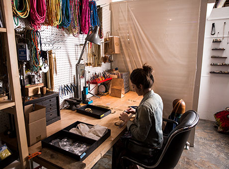 Female at home-based-business sitting at desk making jewelry