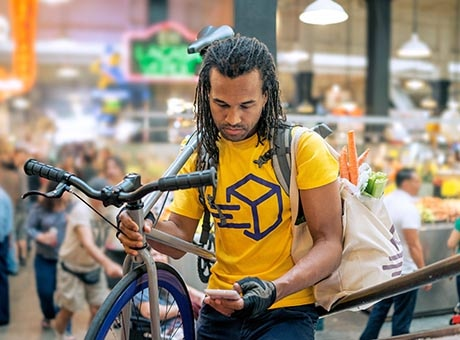 A bicycle courier with a bag of groceries checks his phone outside a market