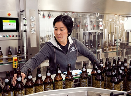 Brewery worker supervises a bottle filling production line