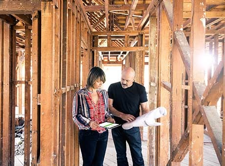 A business owner reviews construction work of a second location with the foreman