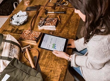 Business owner reviews sales of handmade items on tablet at workbench