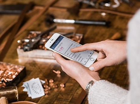 Business owner manages her retail business from her mobile phone