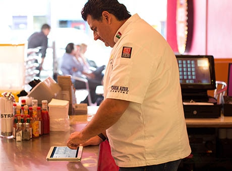 A chef manages accounts on a tablet at cafe counter