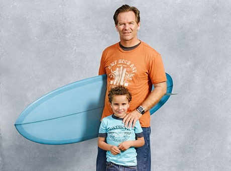 A child care provider poses with a boy and a surfboard