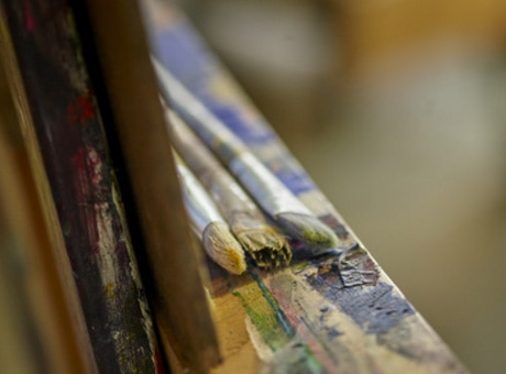 Detailed view of paint brushes on an easel