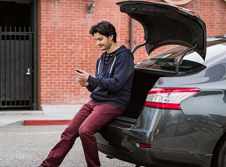 An employee accesses public wifi from his smartphone while traveling by car
