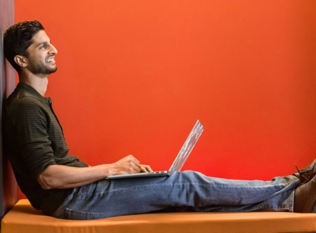 An employee works on his own laptop at the office