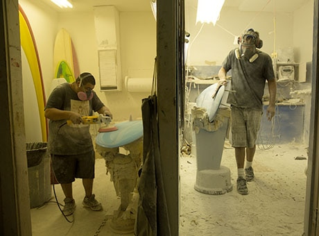 Employees use their own tools to refurbish surf boards