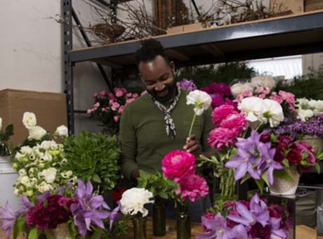 A florist arranges bouquets for display a gravesite