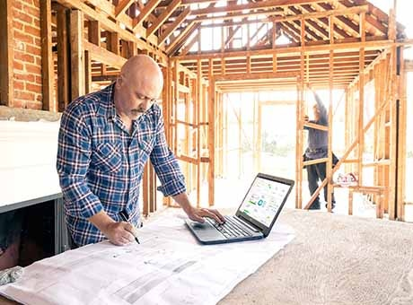 A construction foreman reviews building plans while a seasonal employee works in the background