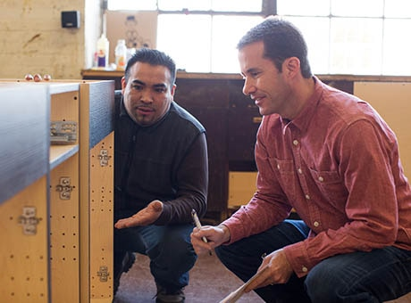 A handyman discusses cabinet repairs with a business owner