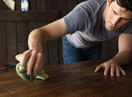 An independent house cleaner polishes a table