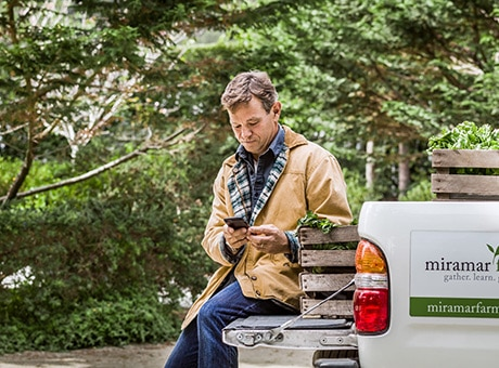 A landscaper checks his phone while sitting on the back of a company truck