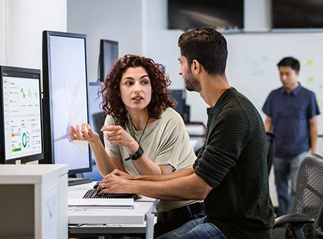 A manager disciplines an employee at his workstation