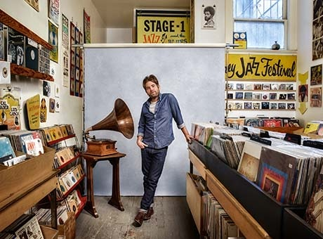 The owner of a sole proprietorship record shop poses in his store