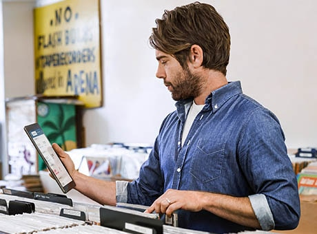 A record store owner updates the inventory on his e-commerce site using a tablet