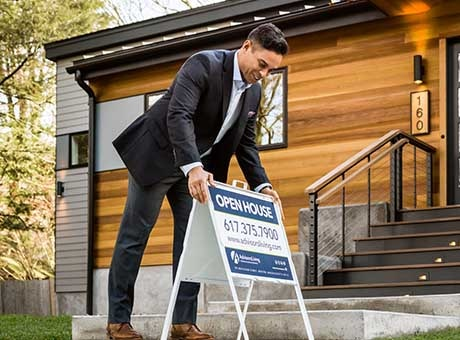 The owner of a rental property places an open house sign outside his property