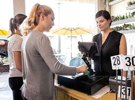 A restaurant cashier rings up customers after their meal