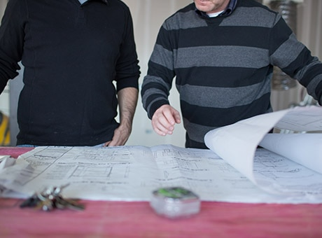 Workers review blueprints for the custom remodeling of a business