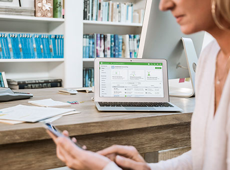 Female Business Owner Accesses Cloud-based Balance Sheet on Electronic Device