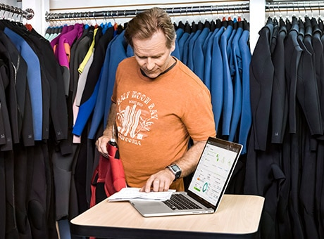 Shop Owner Checks Shopify Sales With QuickBooks Online on Laptop