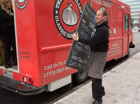Food truck owner hanging up a new menu to distinguish his business from competitors and attract more customers.