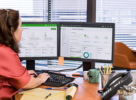 Accountant reviews payroll errors in office with two computer monitors