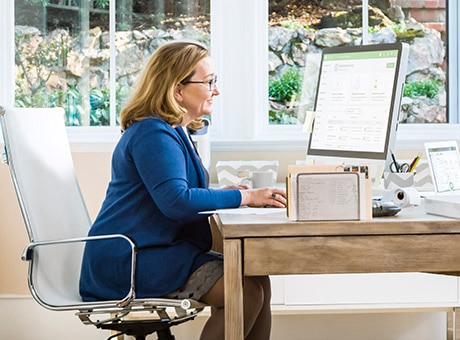 An accountant works with auto-reversing journal entries at her desk