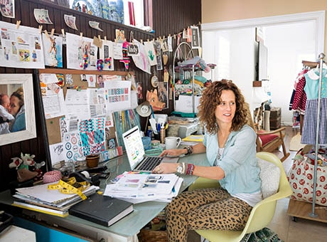 A home-based employee poses in her home office